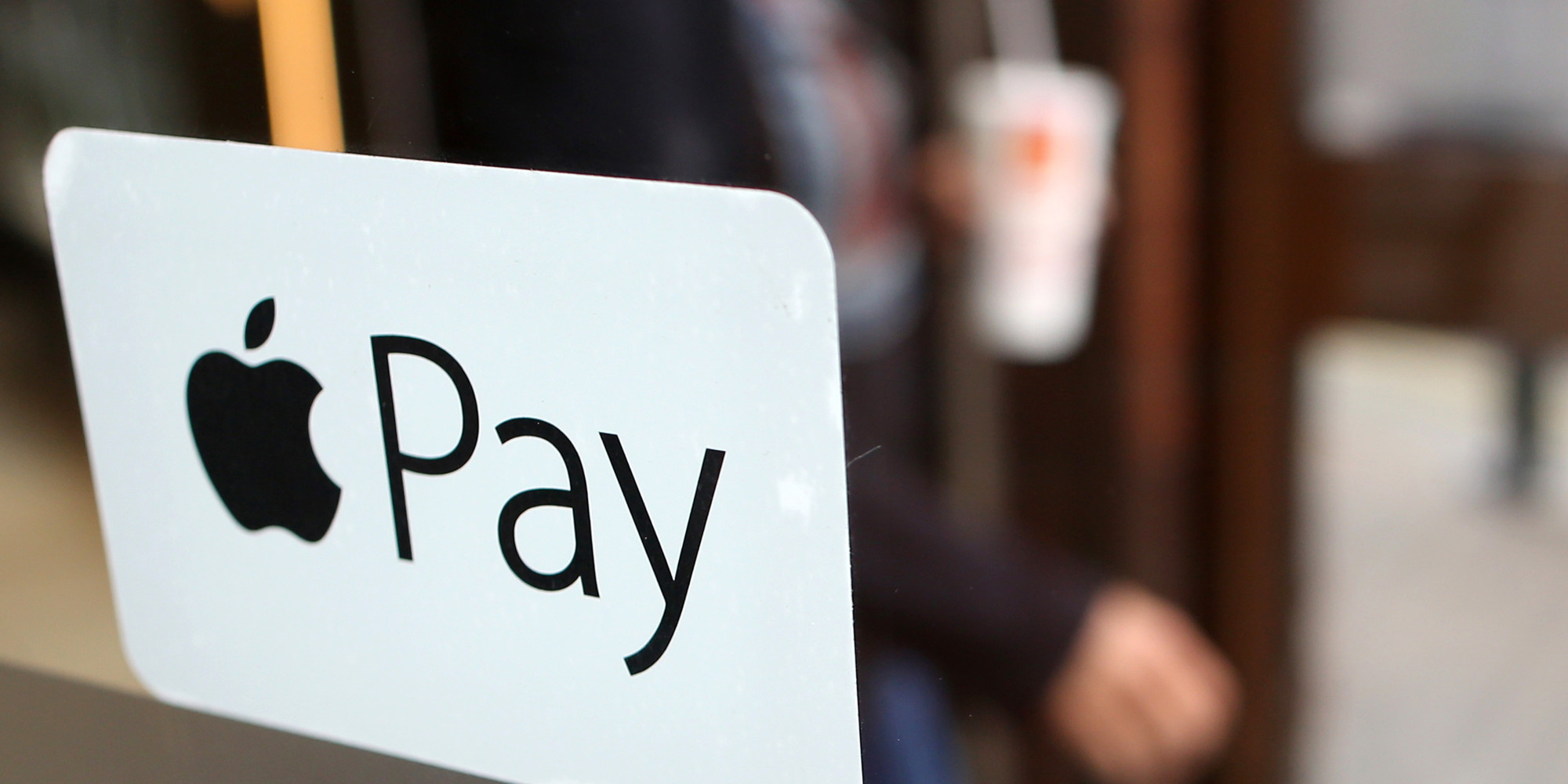 A sign for the launch of the Apple pay system, from Apple.Inc is seen displayed at the entrance to a McDonald's Corp. restaurant in London, U.K., on Tuesday, July 14, 2015. Apple Inc. is making the U.K. the first market outside the U.S. for its digital-wallet system as the company fights for a place in the electronic-payments industry. Photographer: Chris Ratcliffe/Bloomberg via Getty Images
